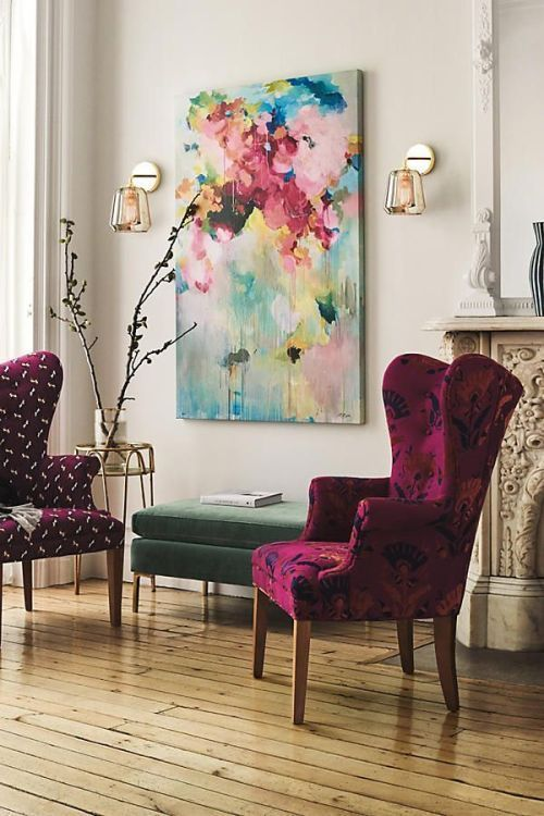 a couple of very bold and colorful upholstered wingback chairs and a bold artwork make the nook vibrant