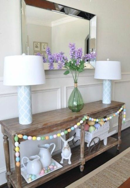 a rustic wooden console decorated with a colorful egg garland, a tray with eggs and a bunny