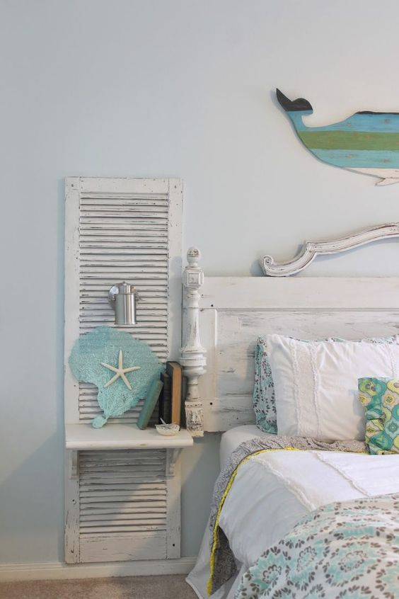 a wall-mounted nightstand for a shabby chic beach bedroom is made of an old shutter and a piece of wood