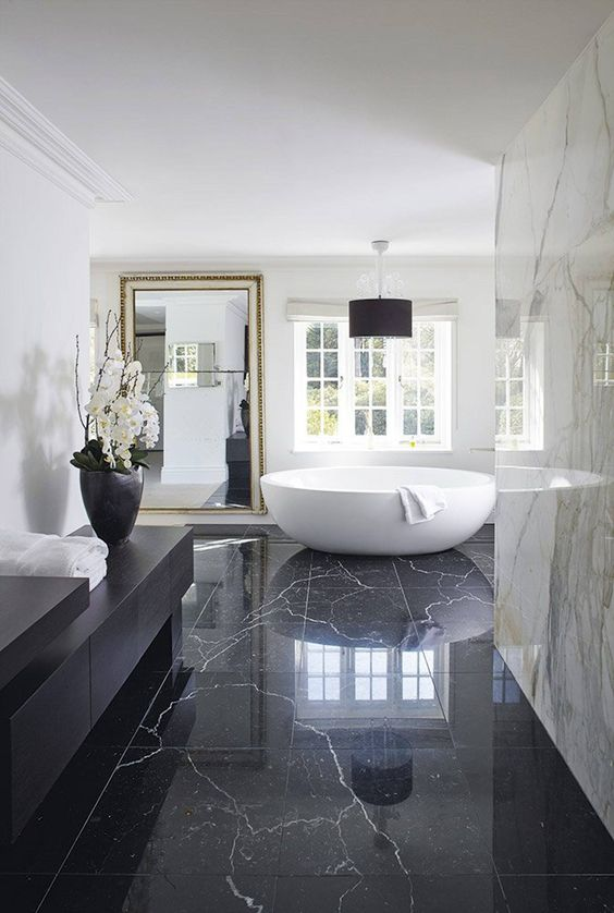 an oversized framed wall mirror adds more glam and chic to this marble bathroom