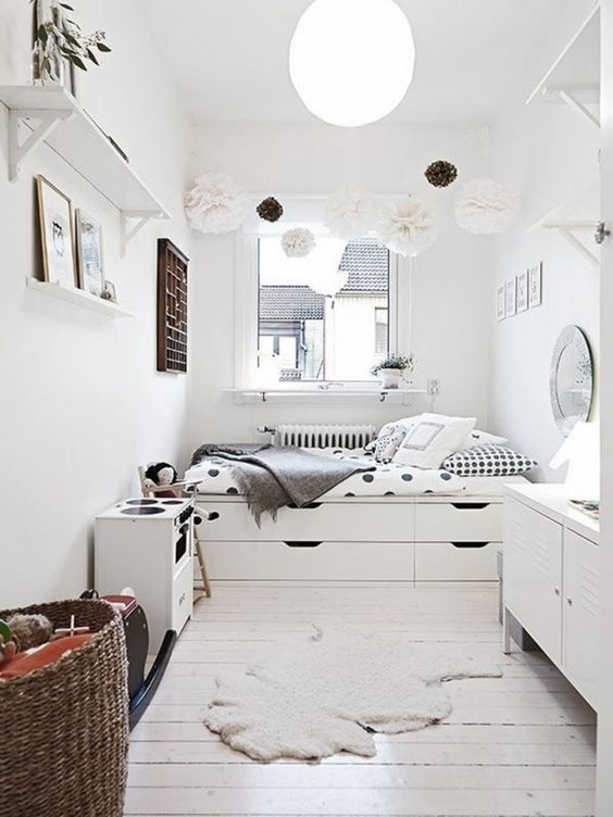 a serene Scandinavian space done with a bed with built in storage drawers is a great idea