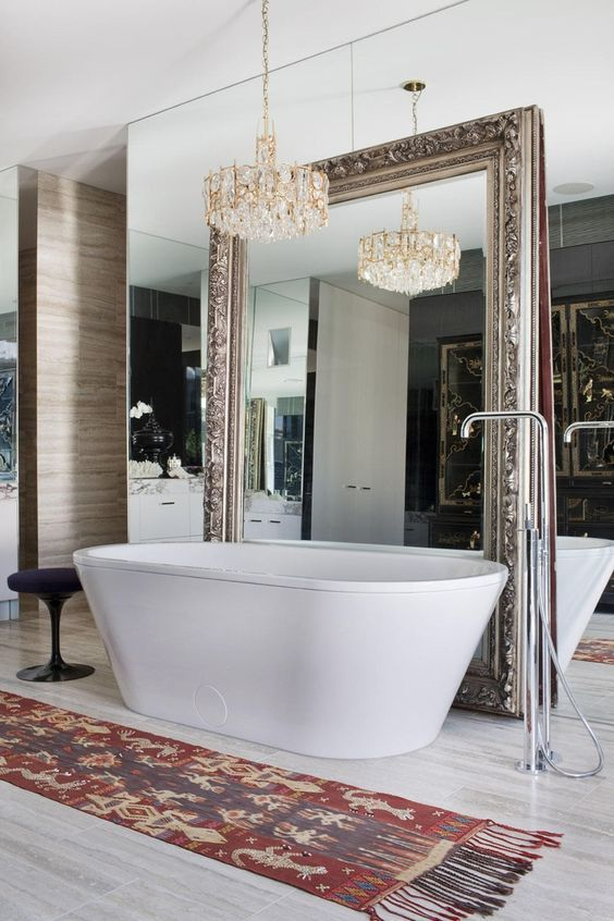 a whole mirror wall with an additional vintage mirror and a gorgeous statement chandelier for a refined feel