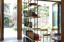 16 an industrial bookshelf of metal and plywood is a great lightweight piece to separate the spaces