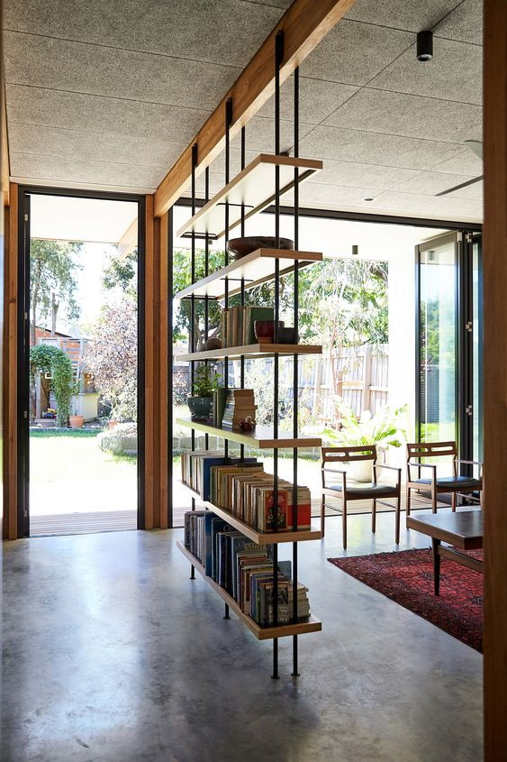 an industrial bookshelf of metal and plywood is a great lightweight piece to separate the spaces