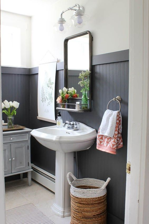 black tall wainscoting is a dominating decor feature in this bathroom that makes the space look bold