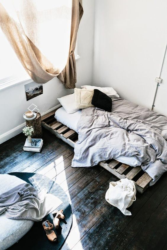 a small industrial bedroom with a pallet bed in the corner and a round ottoman with a rug