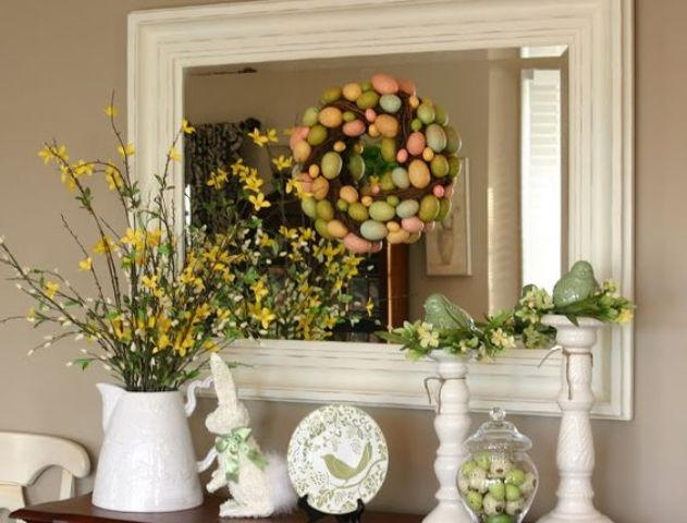 an Easter console with faux blooming branches, a colorful egg wreath, colorful eggs in a jar
