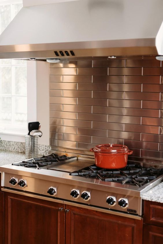 copper colored stainless steel tiles for the cooking zone and a matching cooker for a cool look