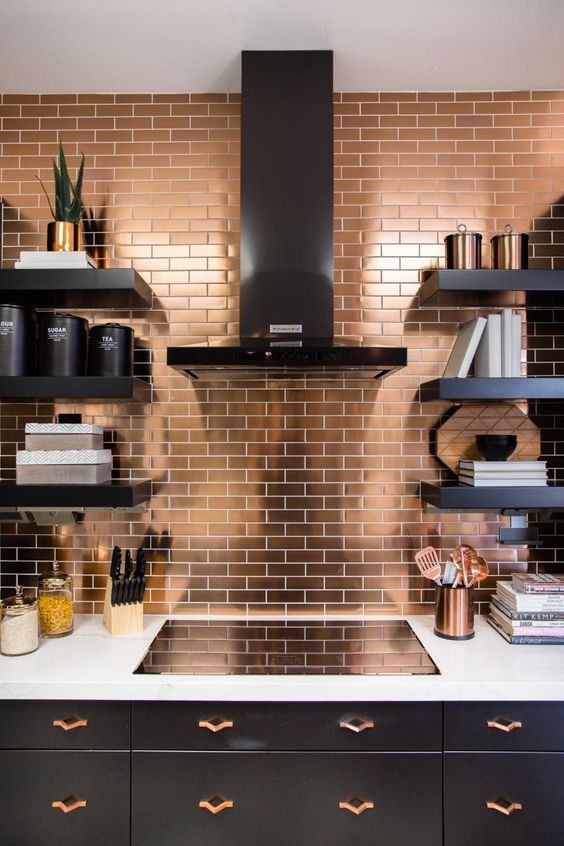 a copper tile backsplash and matching handles in a black kitchen to bring some chic
