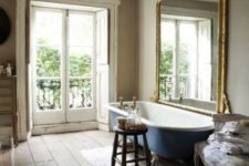 19 a rustic bathroom is made more elegant with an oversized vintage mirror and a gorgeous chandelier