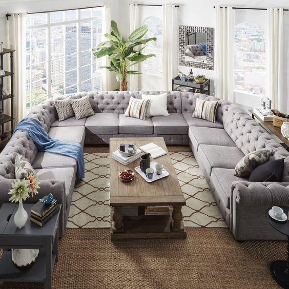 an oversized U shaped grey tufted sofa makes a perfect fit for this unusually shaped living room