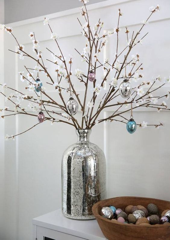 style your console with faux cherry blossom branches and glass egg ornaments plus colorful ones in a wooden bowl