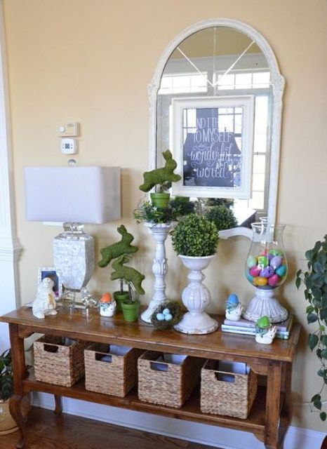 a console with moss bunnies and colorful eggs in a jar for a rustic feel
