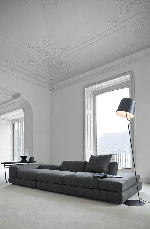 a graphite grey long sectional sofa makes a statement in this refined and airy room with much negative space