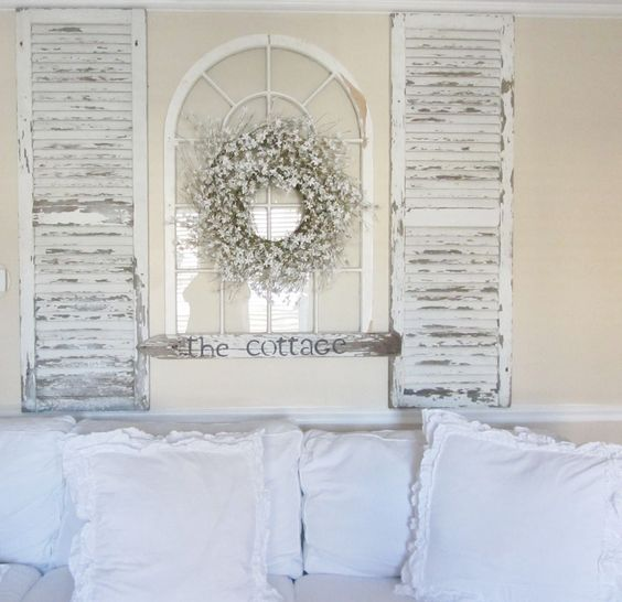 a shabby chic decoration of old shutters and a vintage window plus a floral wreath for a vintage space