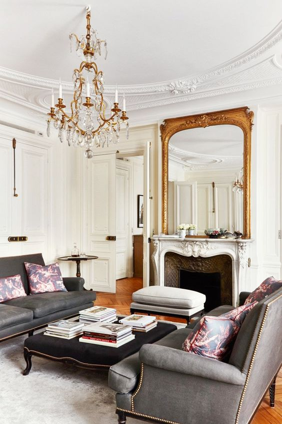 an antique mirror in a gilded frame and a gorgeous chandelier remind of Parisian chic