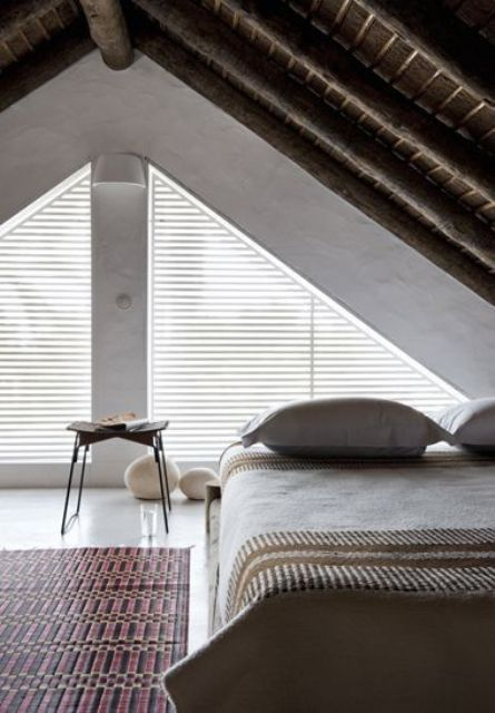 an attic bedroom with a bed placed in the corner, a zen feel and touches bring peacefulness to the space