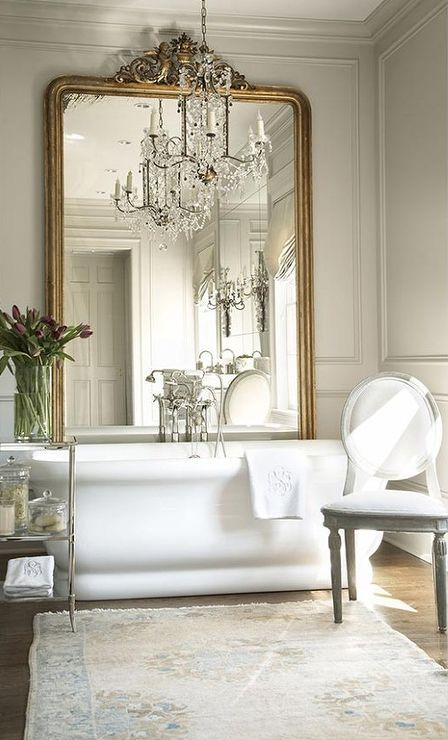 an oversized mirror in a vintage frame makes the bathroom exquisite, and a crystal chandelier adds to the space