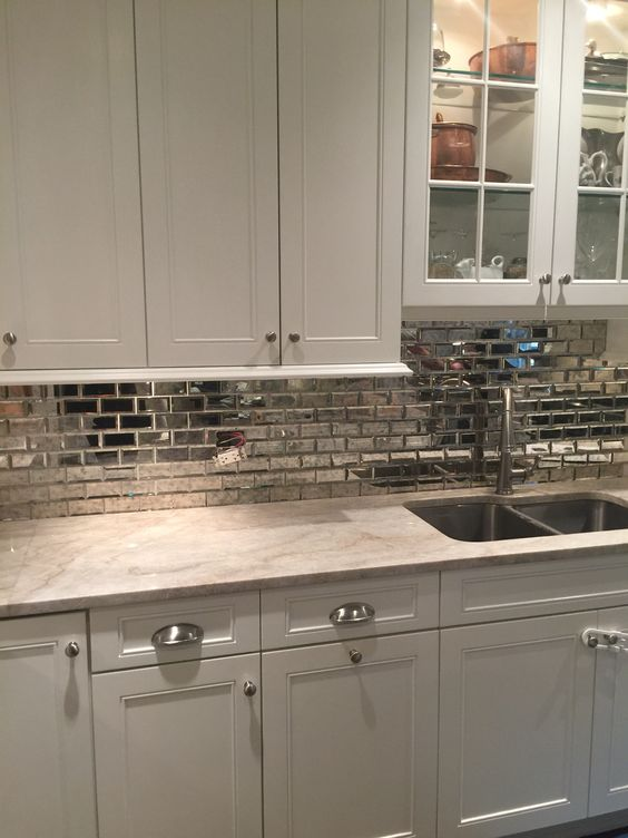 a silver tile backsplash makes this pearly colored kitchen shine on