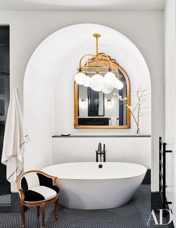 go for a stylish framed mirror in your bathtub niche for an elegant touch