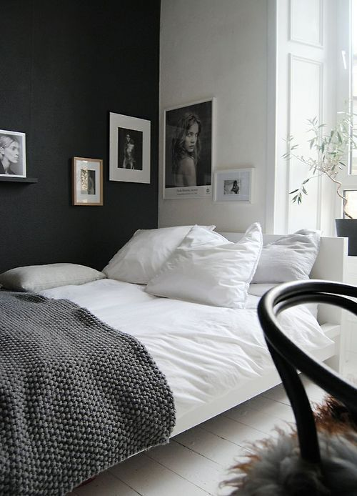a Scandinavian bedroom in black and white, with proper artworks covering the corner