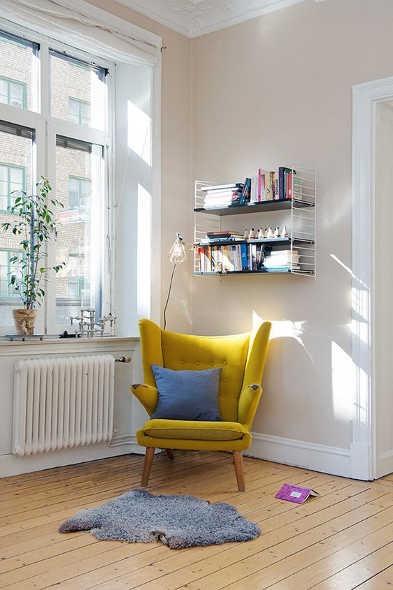 a modern take on a classic wingback in sunny yellow is a great base for a reading space