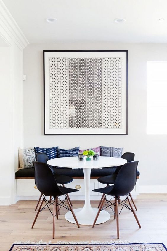 a small mid-century modern dining room with a bold graphic artwork that takes over it