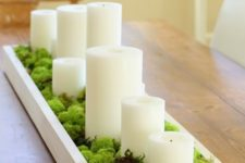 a moss centerpiece with pillar candles in a box is a great idea for any party
