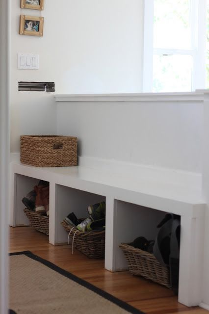 a pony wall with a bench and open storage that separates the entryway and living space