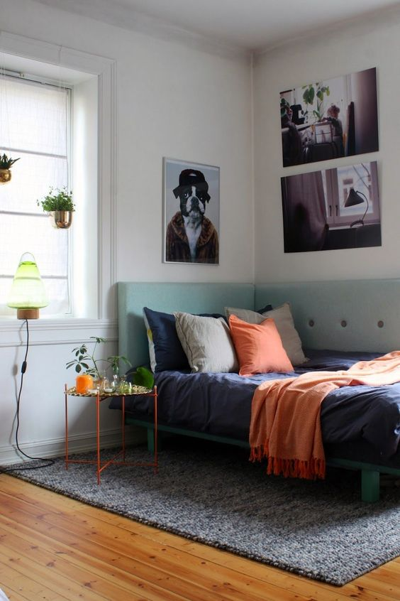 a small and colorful bedroom with a mint bed with a corner headboard and bold touches