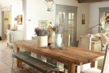 24 a Provence-styled dining room with a reclaimed wooden ceiling with beams and matching furniture