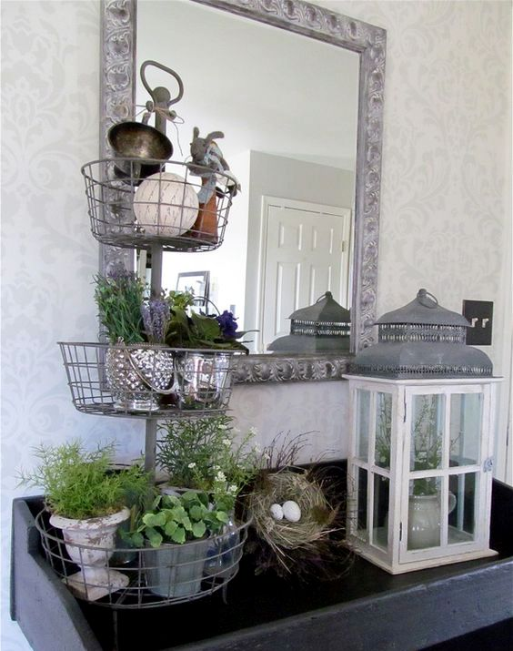 a console with a faux nest with eggs, a lantern and a stand with potted greenery and flowers