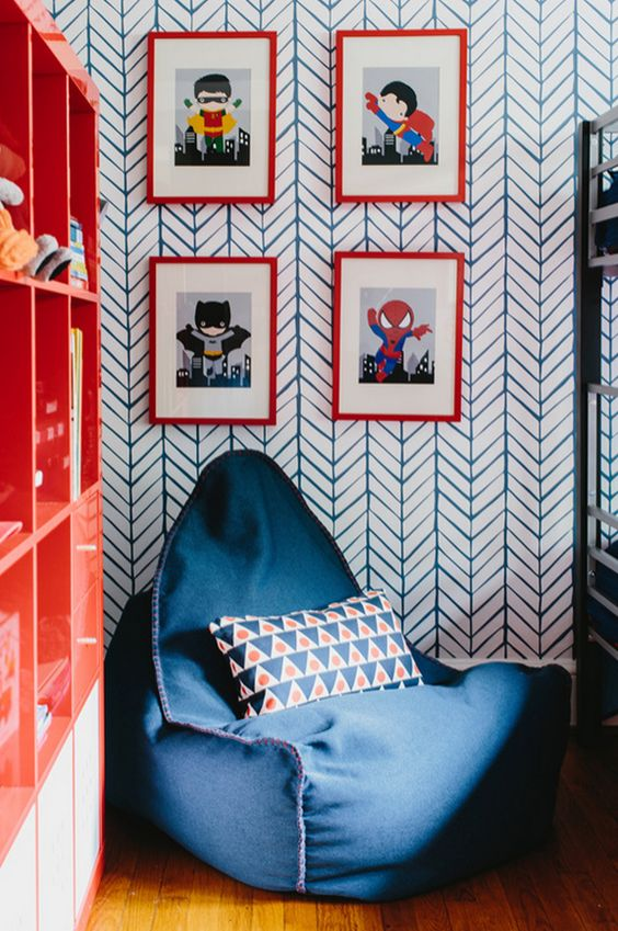 a cool nook with a bean bag chair, colorful super hero posters and a bold bookshelf