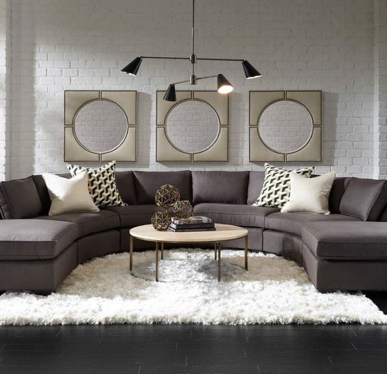 a laconic brown rounded sectional sofa is the base of this room, and everything is built around it
