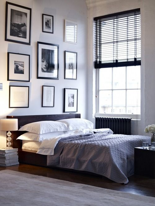 a laconic masculine sleeping space with a gallery wall and dark touches here and there