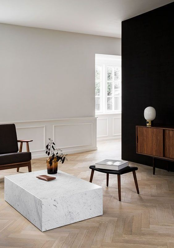 a minimalist living room in black and white and wooden touches lacks only some greenery for a spring feel
