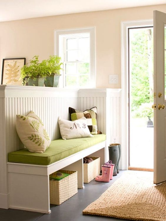 a pony wall with an upholstered bench and functional open storage units for separating the entryway from the rest of the house