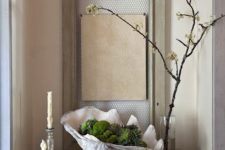 24 a stylish art piece of a porcelain shell, moss and magnolia cones for a chic modern look