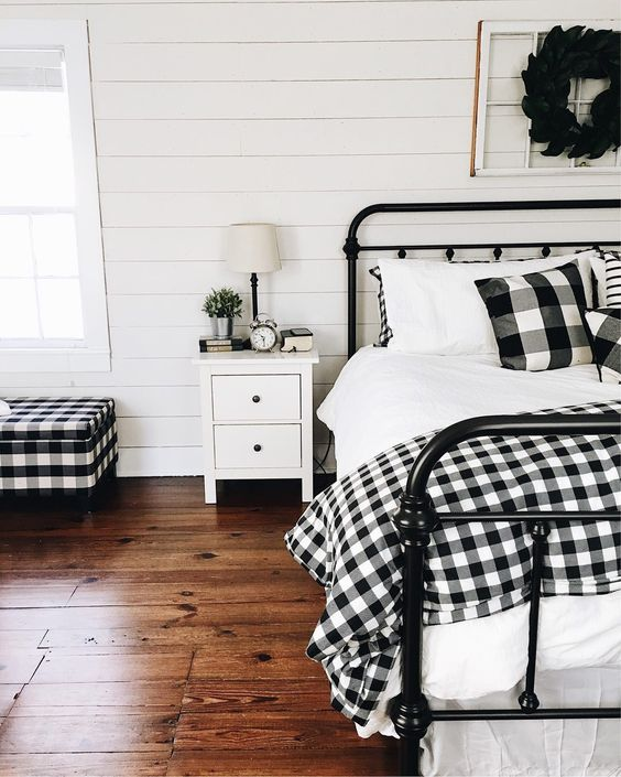 buffalo check pillows, a bedspread and a matching upholstered bench for a cozy farmhouse bedroom