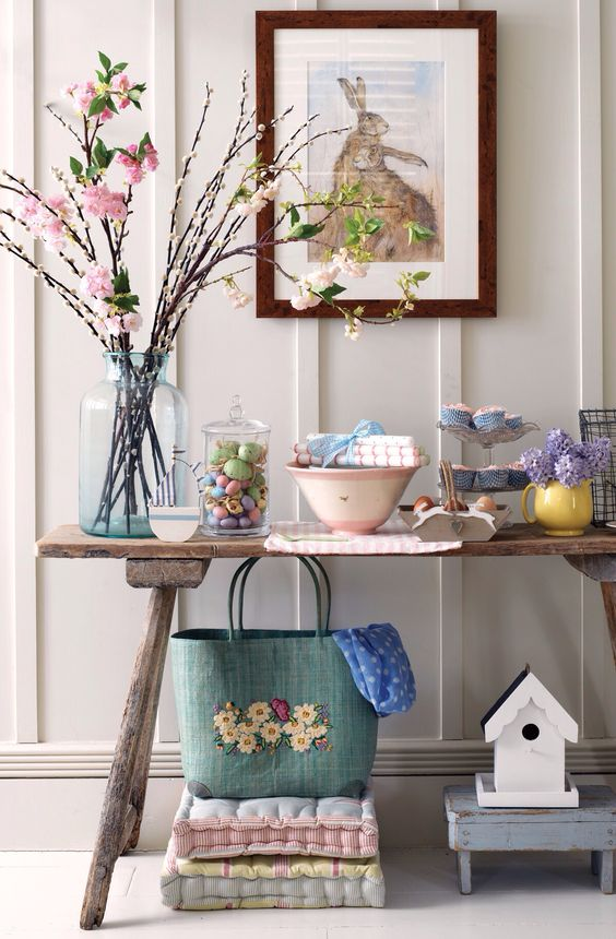 a console with blooming branches, colorful eggs in a jar, bold flowers and textiles