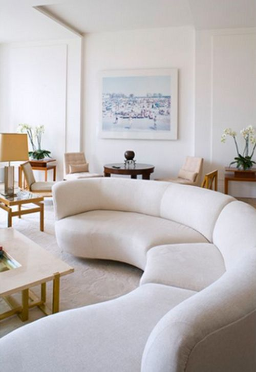 a long rounded creamy sectional sofa adds a whimsy touch to this contemporary space