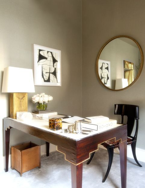 a mid-century modern home office with an artwork and a large round mirror on the wall