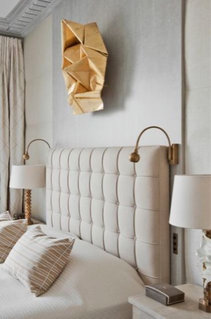 a modern glam geometric sculpture over the bed that echoes lamps