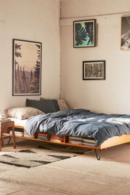 a small industrial bedroom with a hairpin leg bed with storage inside and various artworks
