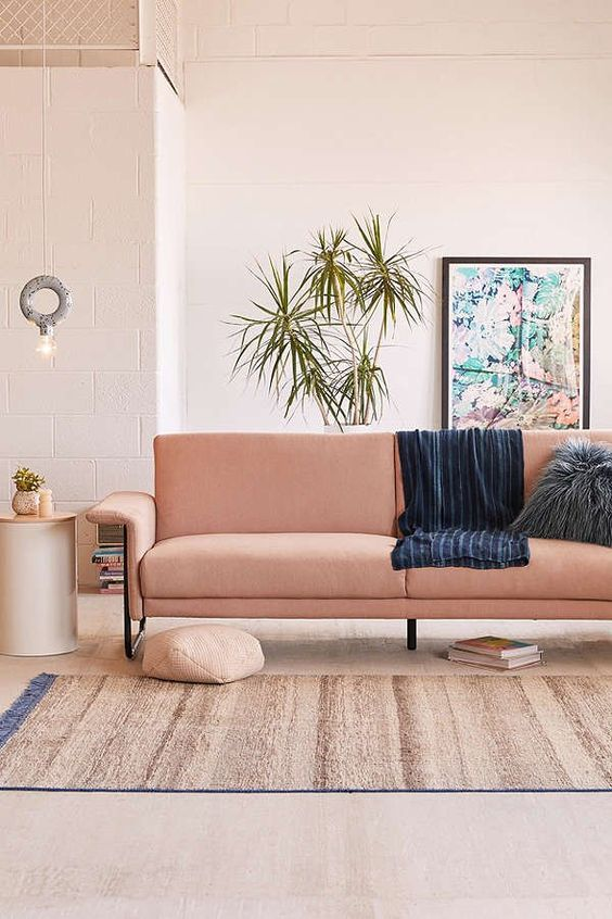 a cozy warm-colored living room with a salmon-colored sofa and potted greenery feels like summer