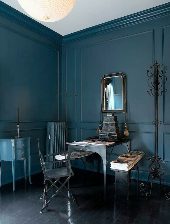 a moody masculine office with a vintage-framed mirror to enliven the space