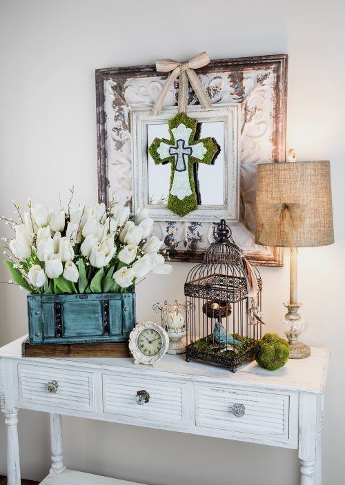 a shabby chic white console with white tulips and willow pussy in the box, a birdcage with a faux nest and bird and a moss cross