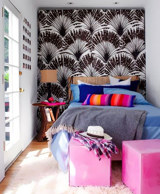 a tiny yet colorful bedroom with a printed wall, colorful cube ottomans and bold bedding