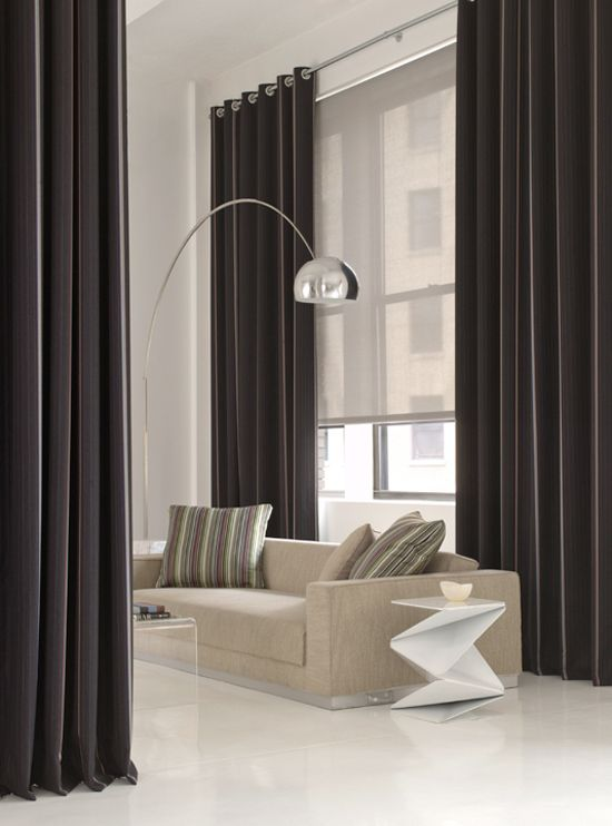 stylish black curtains and an additional semi sheer Roman shade to hide from the sun