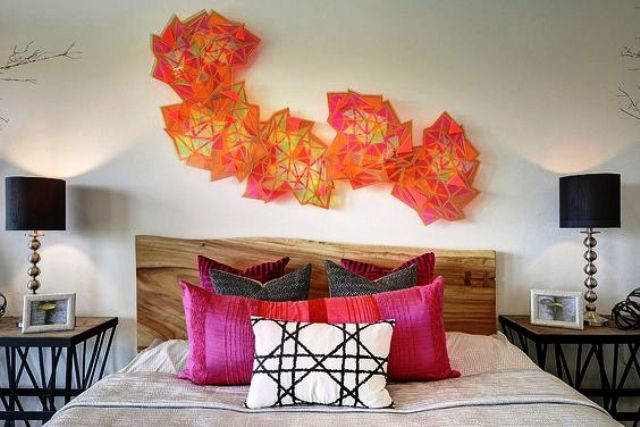 colorful geometric sculptures over the bed make a bold accent